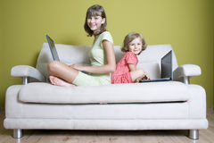 Sisters with laptops on sofa Royalty Free Stock Photography