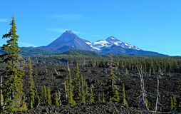 Sisters Lava View. View of North and Middle Sisters peaks from the lava bed at McKenzie Pass, OR - Cascade Range royalty free stock image