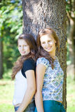 Sisters leaning against a tree Royalty Free Stock Photos