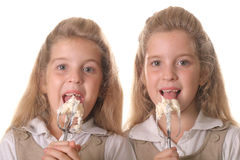 Sisters licking beaters Royalty Free Stock Photo