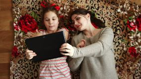 Sisters together look in order to tablet. Sisters lie on the floor and look together at the tablet stock footage