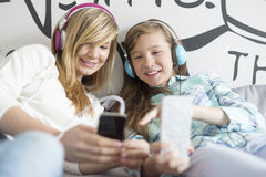 Sisters listening music through headphones at home Stock Photo