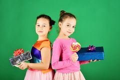 Sisters with lollipops, boxes and bags. Children eat colorful caramels. Sisters with lollipops, boxes and bags. Children eat big colorful sweet caramels opening royalty free stock photography
