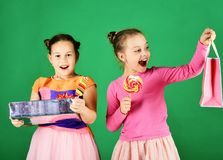 Sisters with lollipops, boxes and bags. Children eat colorful caramels. Sisters with lollipops, boxes and bags. Children eat big colorful sweet caramels opening stock photos