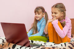 Sisters looking at laptop cartoon Royalty Free Stock Images