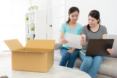 Sisters looking at online shopping parcel list stock image