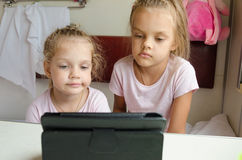 Sisters looking at tablet in the train Stock Photo