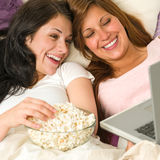 Sisters lying on bed watching funny movie stock photo