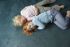 Sisters Lying On Carpet At Home Stock Image