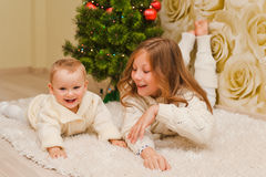 Sisters lying on the carpet, looking at the camera and smiling. Royalty Free Stock Photos