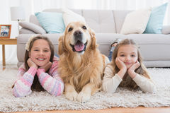 Sisters lying on rug with golden retriever smiling at camera Royalty Free Stock Photography