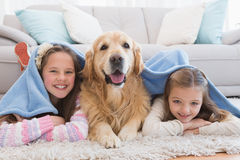 Sisters lying on rug with golden retriever under a blanket Royalty Free Stock Photo