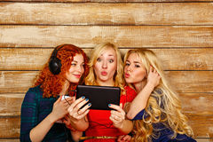 Sisters make fun selfie, listening to music on headphones Royalty Free Stock Photography