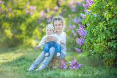 Sisters with mother playing in blooming lilac garden. Cute little girls with bunch of lilac in blossom. Kid enjoying happy childho royalty free stock images