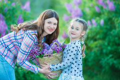 Sisters with mother playing in blooming lilac garden. Cute little girls with bunch of lilac in blossom. Kid enjoying happy childho Stock Photography