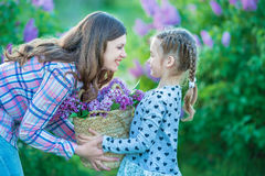 Sisters with mother playing in blooming lilac garden. Cute little girls with bunch of lilac in blossom. Kid enjoying happy childho stock photos
