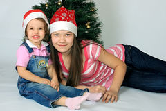 Sisters are in new-year caps. A sisters in the cap of Santa Claus Royalty Free Stock Photos