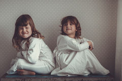 Sisters in nightgowns play on  old trunk. Siblings sisters in nightgowns quarrel, swear and play on an old trunk Royalty Free Stock Image