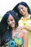 Sisters - one gives neck massage to another Royalty Free Stock Photos