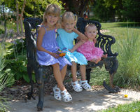 Sisters on park bench stock image
