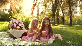 Sisters picnic. Two little cute sister at a picnic. They eat pear and apple. Outdoor Activities. For picnic basket Balloons tied stock footage