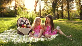 Sisters picnic. Two little cute sister at a picnic. Outdoor Activities. For picnic basket Balloons tied. Girls are fooled stock video