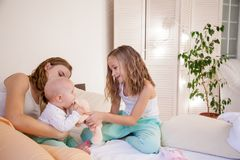 Sisters play with the baby on the bed in the bedroom. 1 Royalty Free Stock Image