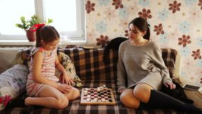 Sisters playing checkers. Sisters play checkers at home on the couch and next to them cats stock footage