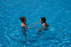 Sisters play in the pool. Sisters play in the swimming pool on a summer sunny day Stock Photography