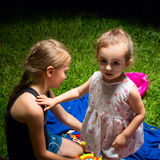 Sisters play sitting on the grass. Stock Photo