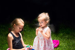 Sisters play sitting on the grass. Royalty Free Stock Photography