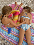 Sisters play with sun lotion Royalty Free Stock Photo