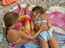 Sisters play with sunscreen on the stone beach Royalty Free Stock Photography