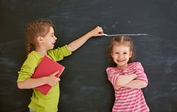 Sisters play together. Two children sisters play together. Kid measures the growth on the background of blackboard. Concept of education Royalty Free Stock Photography