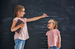 Sisters play together. Two children sisters play together. Kid measures the growth on the background of blackboard. Concept of education Stock Image