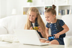 Sisters play video game. Portrait of a cute little sisters play video game Stock Image
