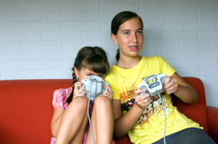 Sisters play video game - tension. Two girls playing video game. One teen one child. White wall and red sofa stock images