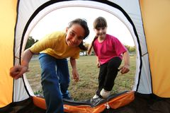 Sisters Playfully Running Into Tent Outdoors Royalty Free Stock Images