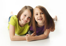 Sisters playing. Cute young sisters isolated on white in studio Stock Photos