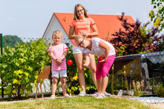 Sisters playing bocce in garden front or their home Stock Photo