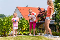 Sisters playing bocce in garden front or their home Stock Image
