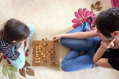 Sisters are playing chess. On carpet stock images
