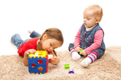 Sisters playing on the floor. Cute sisters playing with a plastic toy Royalty Free Stock Photos