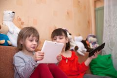 Sisters playing games on tablets. Two sisters playing games on tablets in children`s room stock photos