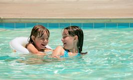 Sisters Playing in a Pool Outdoors Royalty Free Stock Images