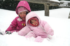 Sisters playing in the snow. During a cold winter storm Royalty Free Stock Images