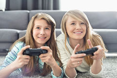 Sisters playing video games in living room Royalty Free Stock Photo
