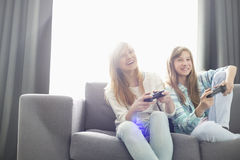 Sisters playing video games on sofa Stock Photography