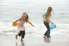 Sisters Playing In Water At Beach royalty free stock images
