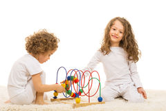 Sisters playing with wooden toy home Stock Image